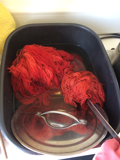 red hanks of wool being taken out of pot