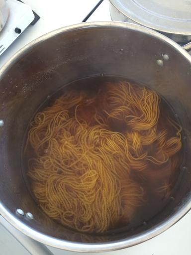 yellow hanks of wool in pot
